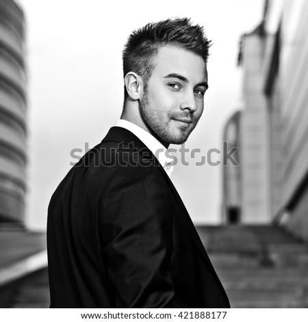 Black-white portrait of beautiful young man outdoor.