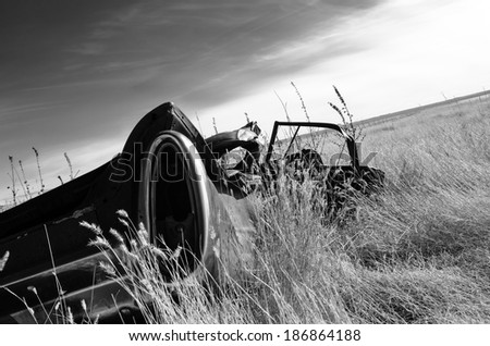 Black & white rusted abandoned car in a field - stock photo