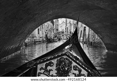 black white view from inside gondola in Venice passing under endless city bridges on busy tourist waterway