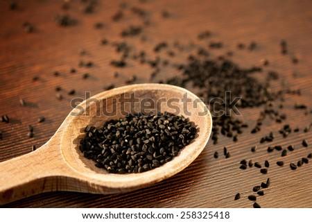 Black whole Nigella Sativa seeds portion on wooden spoon macro, Black cumin raw spice heap in day light, horizontal orientation, nobody. Polish name czarnuszka siewna. - stock photo