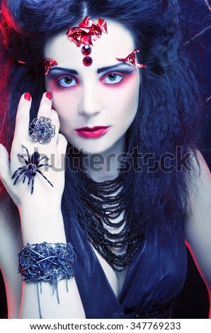Black widow. Young woman in dark artistic image posing with spider