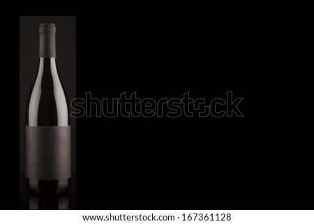 Black wine bottle on black background - stock photo