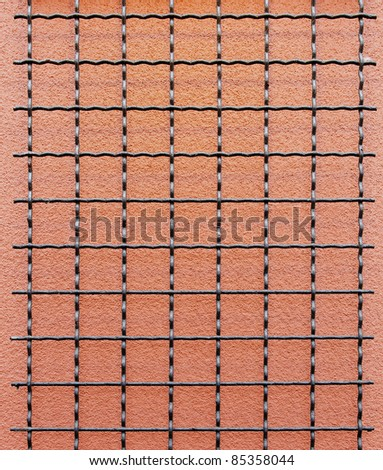 Black wire grid against a salmon stucco wall - stock photo