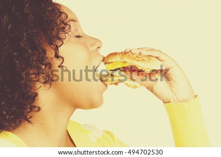 Black woman biting hamburger sandwich