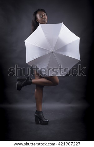 Black woman covered by white umbrella