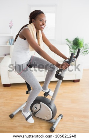 Black woman doing exercise bike while smiling in a living room - stock photo