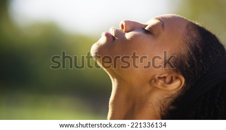 Black woman feeling the sun shine on her face - stock photo