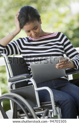 Black Woman in a wheelchair reading a Digital Tablet