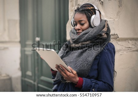 Black woman in blue coat listening to music from her tablet