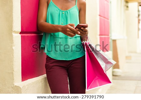 Black woman in Casco Antiguo - Panama City with shopping bags. The girl leans on a wall and types message with her phone on social network.  - stock photo