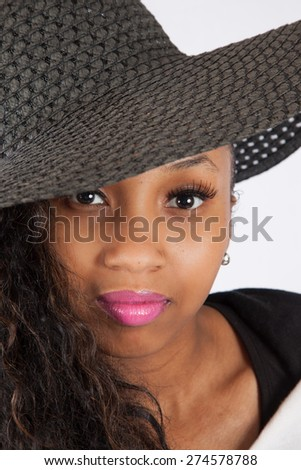 Black woman in hat, looking thoughtfully at the camera - stock photo