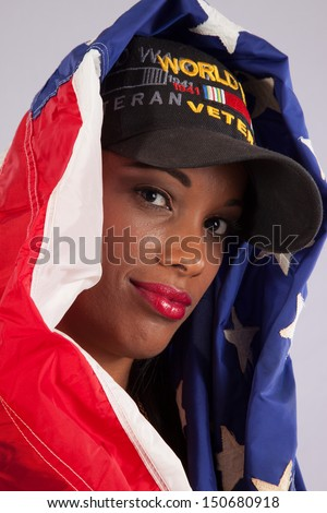 black woman in her grandfathers hat, and wrapped in a US flag, remembering and taking pride in his service to the United States in WW 2