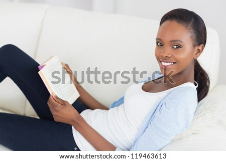Black woman looking at camera while holding a book in a living room