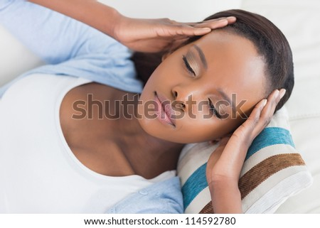 Black woman lying while having hands on temples in a living room - stock photo