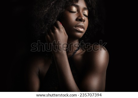 black woman on a black background. evening makeup - stock photo