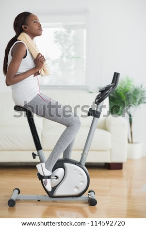 Black woman on an exercise bike holding a towel in a living room