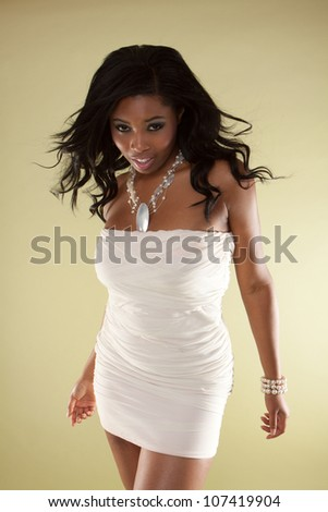 black woman on yellow backgound wearing dress - stock photo