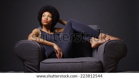 Black woman sitting in chair thinking - stock photo