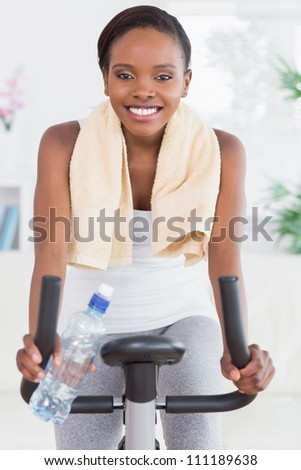 Black woman sitting on an exercise bike in a living room - stock photo