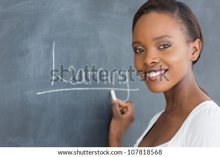 Black woman smiling while looking at camera in a classroom - stock photo