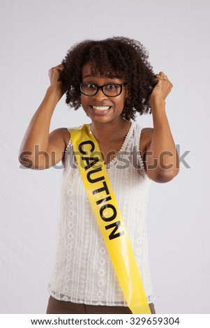 Black woman smiling with Caution tape wrapped around her - stock photo