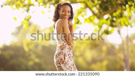 Black woman standing and smiling outdoors - stock photo