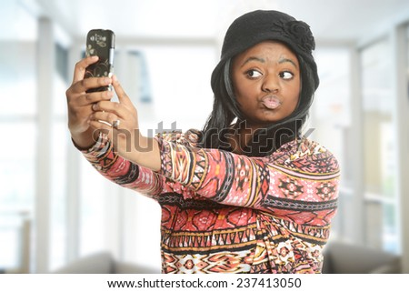 Black woman taking a selfie inside an office building - stock photo