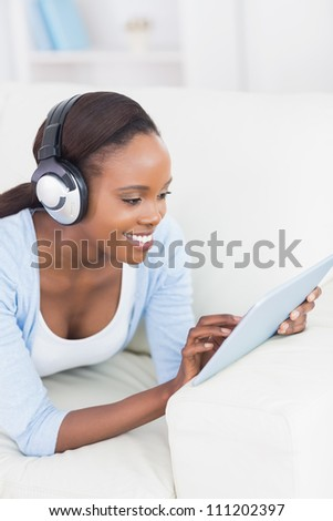 Black woman using a tablet computer in a living room