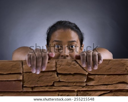 Black woman, with a look of surprise, from behind a brick wall - stock photo