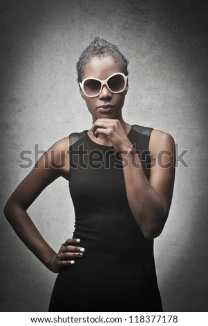 Black woman, with a pair of white sunglasses, posing in black - stock photo
