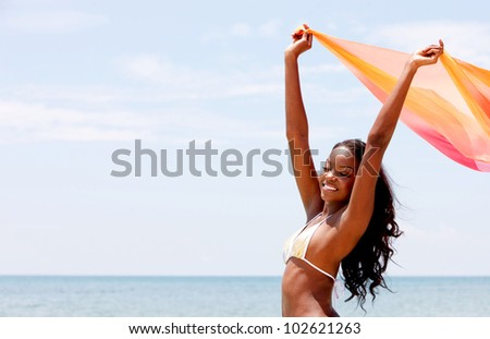 Black woman with a sarong at the beach feeling the wind