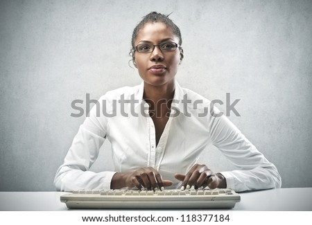 Black woman, with a white shirt, using a computer keyboard - stock photo