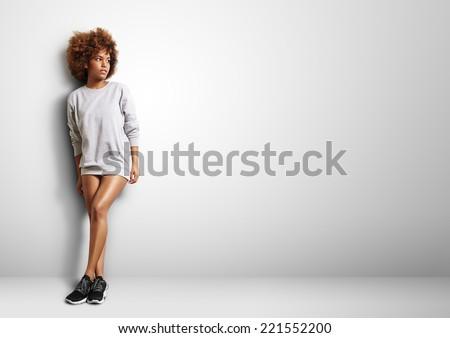 black woman with curly hair wearing sweatshirt like a dress - stock photo