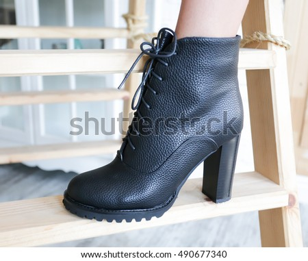 Black women boots on wooden background