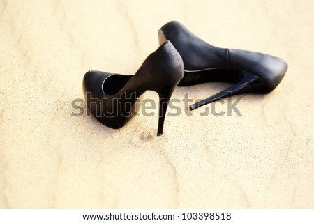 Black women's high heels are in the sand on a sunny summer day, isolated - stock photo