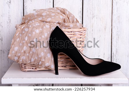 Black women shoes and scarf on bench on wooden background - stock photo