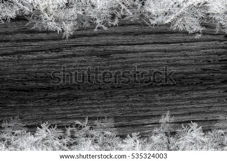 Black wood texture with snowflakes close-up background.