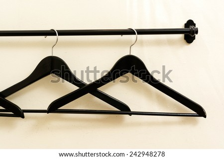 Black wooden hanger on the white wall background - stock photo