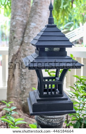 Black woodern lantern lamp with light bulb inside in the green garden forest environment - stock photo