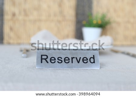 "Black word ""Reserved"" on flat stainless sign, put on table cloth with small decoration vase, porcelain plate, napkin and cutlery in background. Table setting."