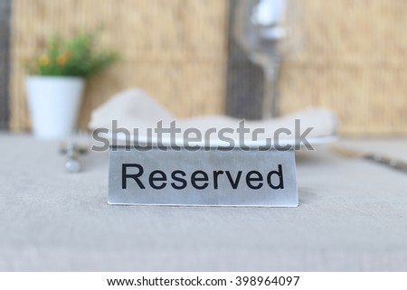 "Black word ""Reserved"" on flat stainless sign, put on table cloth with wine glass, small decoration vase, porcelain plate, napkin and cutlery in background. Table setting."