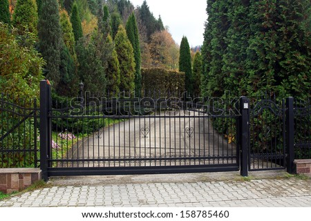 black wrought gate to property with garden in the background - stock photo