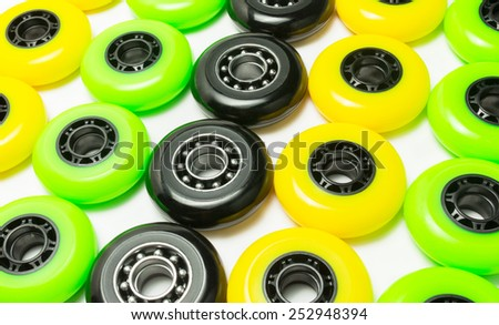 Black, yellow and green color inline skate wheels laying on white background - stock photo