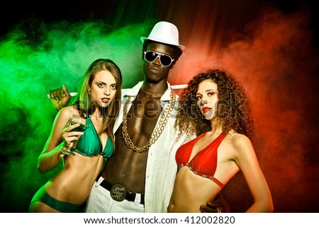 Black young rapper with two girls in bikini red green at club - stock photo