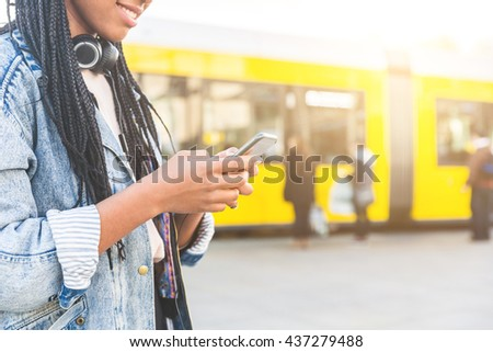 Black young woman typing on smart phone in Berlin. Focus on the hands holding the phone. Blurred people and tram in Alexanderplatz on background.