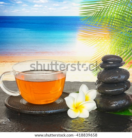black zen stones with cup of tea and flowers with sunny beach in background - stock photo