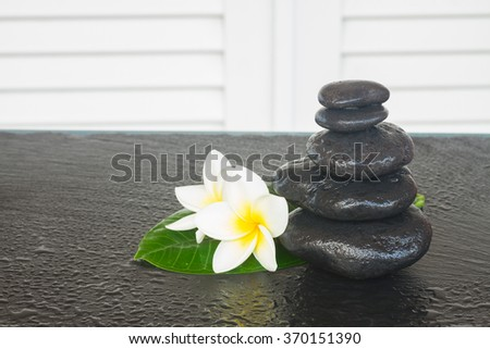 black zen stones with frangipani flowers on black table - stock photo