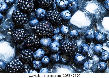 Blackberries and blueberries in ice on a dark background, selective focus - stock photo
