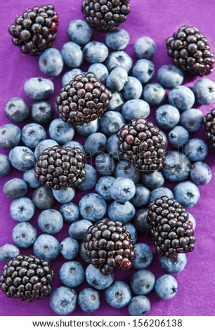 Blackberries and blueberries on a purple background - stock photo