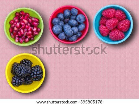 Blackberries, blueberries,  raspberries and pomegranate seeds in colorful bowls, viewed from above, on pink surface